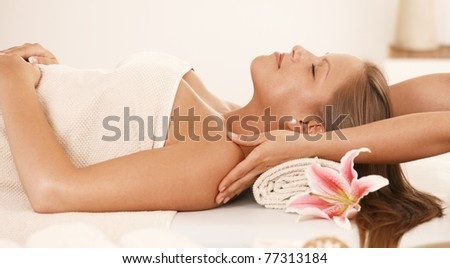 Young woman lying on bed in day spa, enjoying neck massage.?