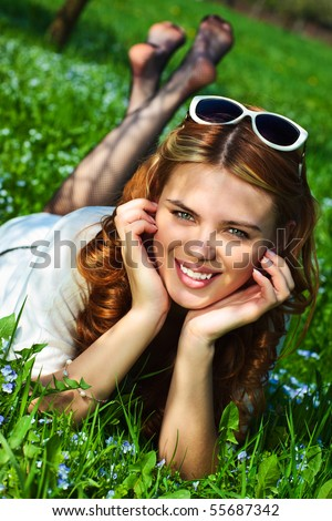 Young woman lying on grass fashion portrait.