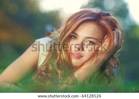 Young woman lying on grass portrait.