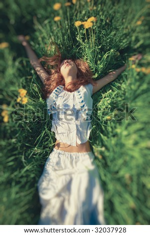 Young woman lying on grass. Top wide angle view. Selective focus effect.