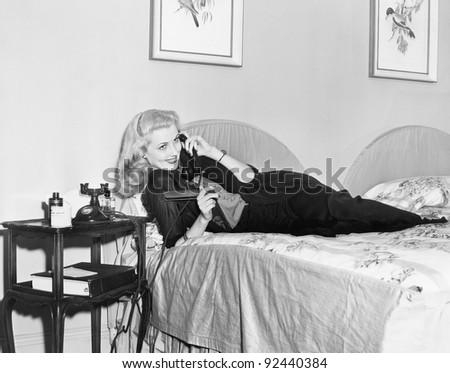 Young woman lying on her bed in the bedroom and talking on the telephone