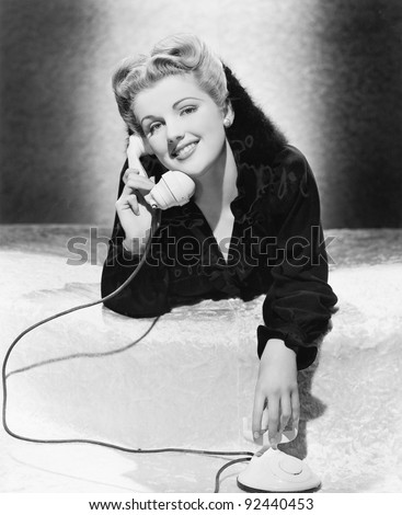 Young woman lying on her stomach and talking on the telephone