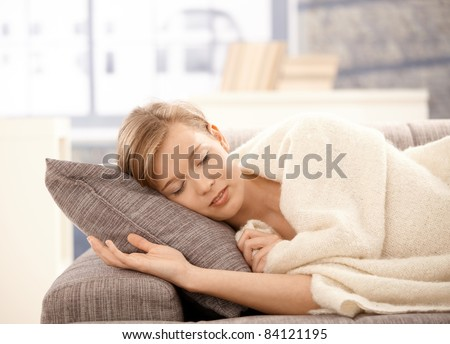 Young woman lying on sofa at home, sleeping covered with warm blanket.?