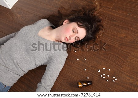 Young woman lying on the floor at home after an overdose of pills.