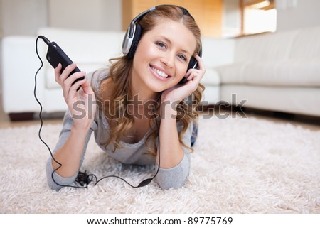 Young woman lying on the floor enjoying music