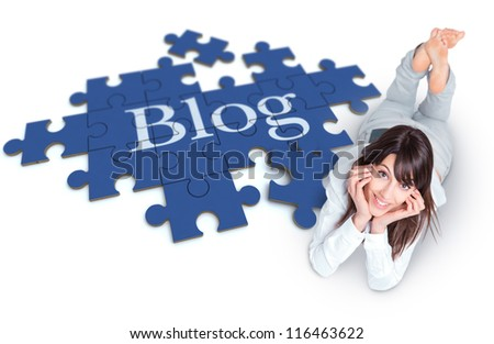 Young woman lying on the floor with a puzzle forming the word Blog - stock photo