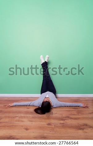 Young woman lying on the floor with her feet up the wall, plenty of copy space to add text, frame or even a TV.