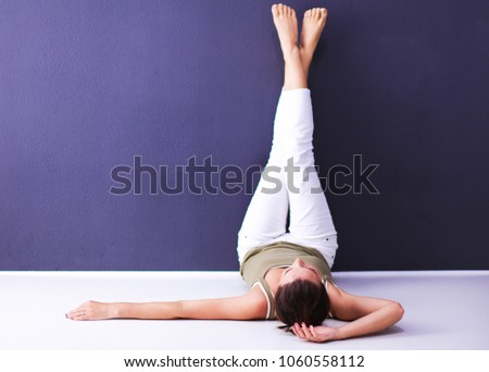 Young woman lying on the floor with legs up