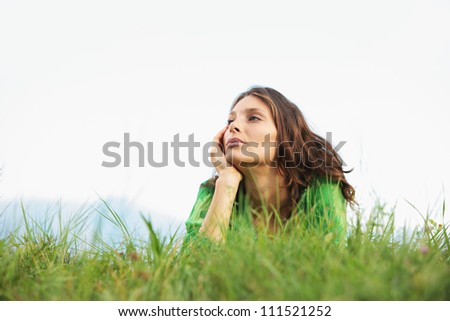 Young woman lying on the grass looking at the sky