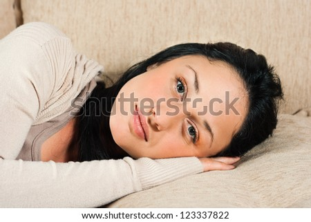 Young woman  lying on the sofa and looking at camera,Beautiful young woman