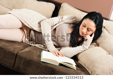 Young woman lying on the sofa and reading a book,Reading a book