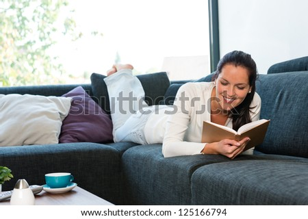 Young woman lying reading book couch sofa living room - stock photo