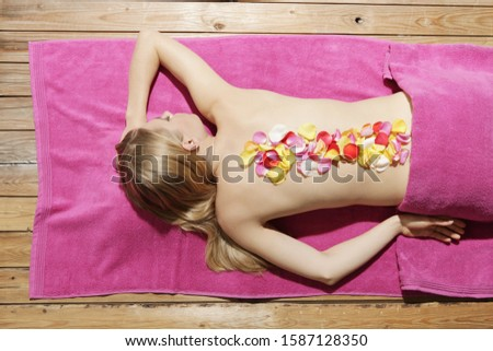 Young woman lying with flower petals on her back