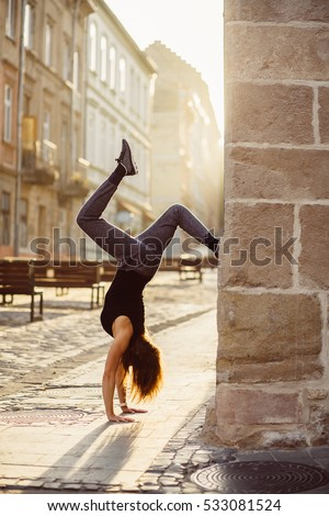 Young woman make handstand  in the summer sunny morning. Handstand exercise. Conception of youth and energy. Vertical.