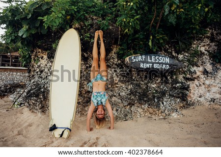 Young woman make handstand near surfboard on the beach. Handstand exercise. Conception of youth and energy. Horizontal