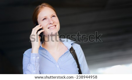 Young woman makes a phone call as she walks through an underpass in a city center.