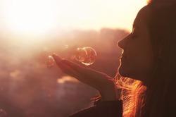 Young woman makes a wish. Cityscape background at sunset.