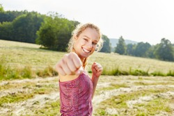 Young woman makes fist while boxing as a workout in nature