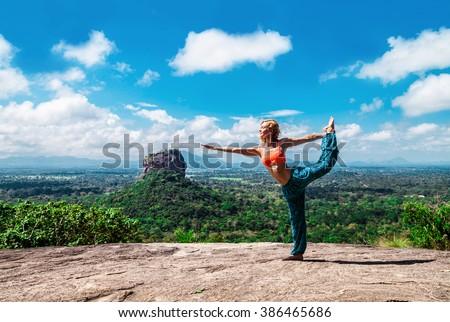 Young woman makes yoga pose on the mountain Pidurangala Rock, Sri Lanka. Sigiriya