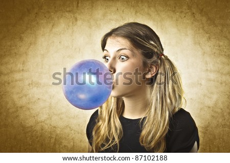 Stock Photo Young woman making a big bubble with a chewing gum