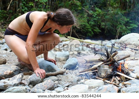 Young woman making a fire on pebble beach