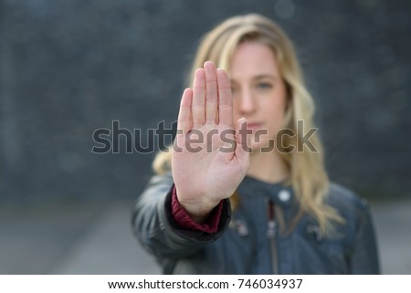 Young woman making a halt or stop gesture with the raised palm of her hand as she bars access or brings an end to something with focus to her hand