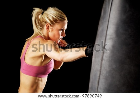Young woman making a hard punch on a punching bag. Isolated on black.
