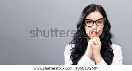 Young woman making a quiet gesture on a solid background