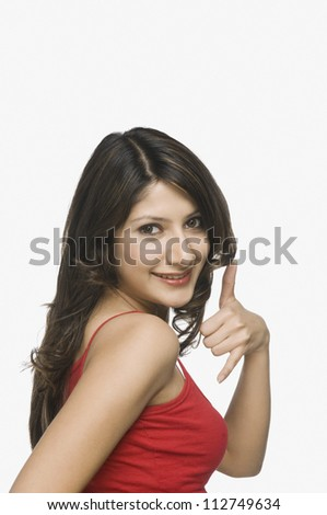 Young woman making a telephone gesture