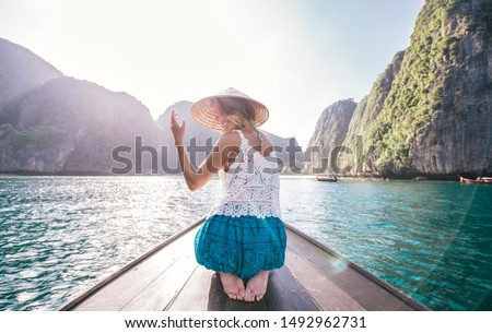 Young woman making a tour on the long tail boat, going to phi phi island