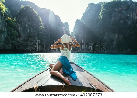 Young woman making a tour on the long tail boat, going to phi phi island #1492987373