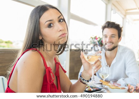Young woman making an exasperated expression gesture on a bad date at the restaurant #490194880