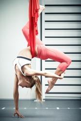 Young woman making antigravity yoga exercises