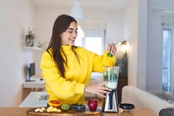 Young woman making detox smoothie at home. Girl making smoothie of fruit and vegetables. Healthy way of life. Happy girl using blender to make smoothie