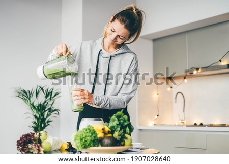 Young Woman Making Detox Smoothie At Home. Woman pouring smoothie to glass. healthy food concept