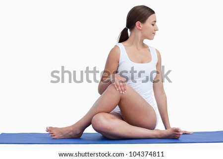 Young woman making exercises on her yoga mat against a white background