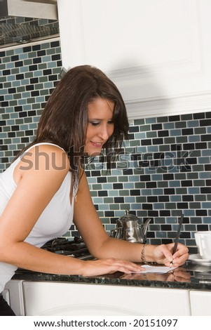 Young woman making her shopping list in the kitchen