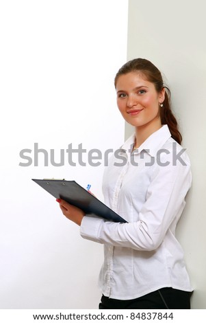 Young woman making notes against wall
