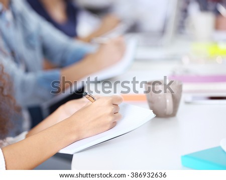 Young woman making notes at the office meeting #386932636