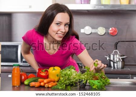 Young  woman making salad at domestic kitchen