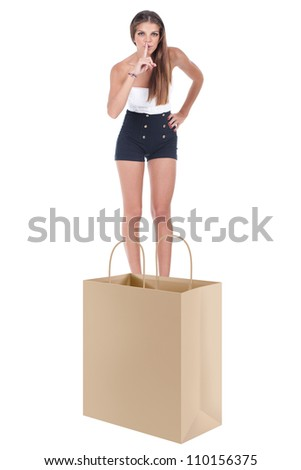 young woman making silence sign on top of a n open shopping bag