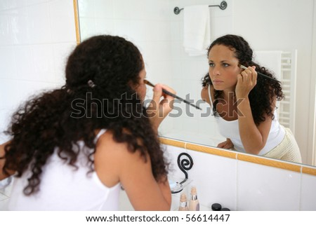 Young woman making up in a bathroom