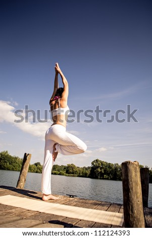young woman making yoga exercise at a lake