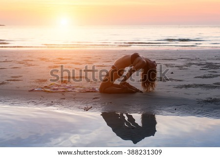 Stock Photo Young woman making yoga exercises on the beach in the setting sun.