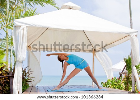 young woman making yoga on the beach