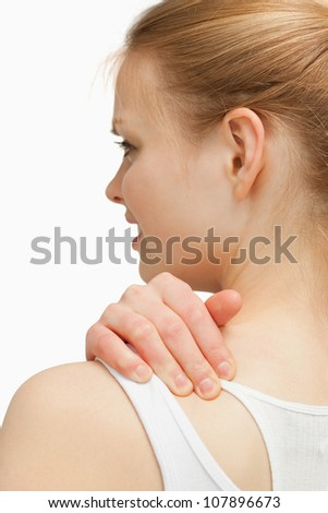 Young woman massaging her nape against white background
