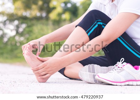 Young woman massaging her painful foot from exercising and running #479220937