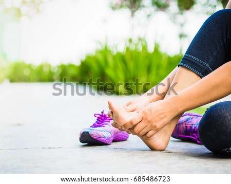 Young woman massaging her painful foot from exercising and running Sport  and excercise concept. #685486723