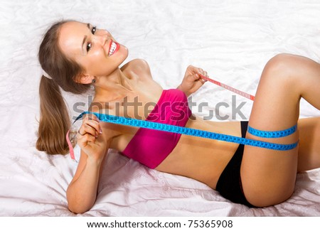 Young woman measures her body on white fabric