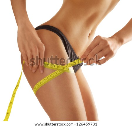 young woman measures her thigh. Isolated. Slim waist with a tape measure around it
